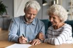 elderly couple working on a document